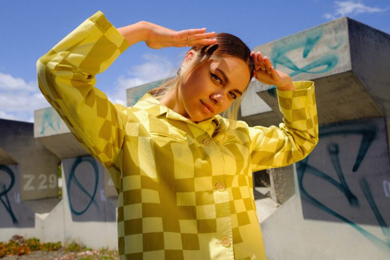 RIIKI press photo wearing a yellow and grey outfit
