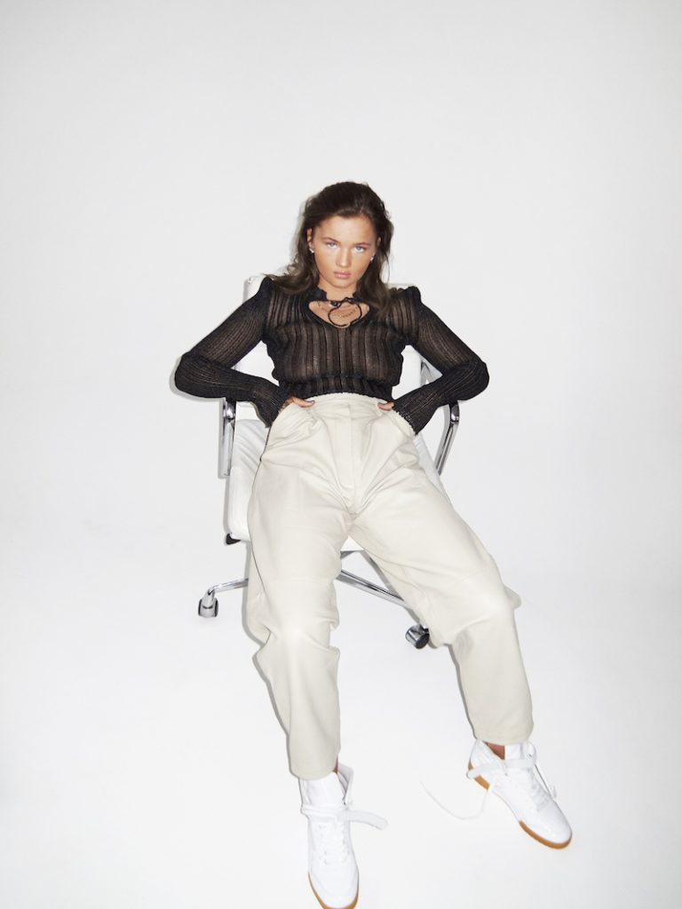 RoseeLu press photo sitting in a chair wearing a black and beige outfit wearing