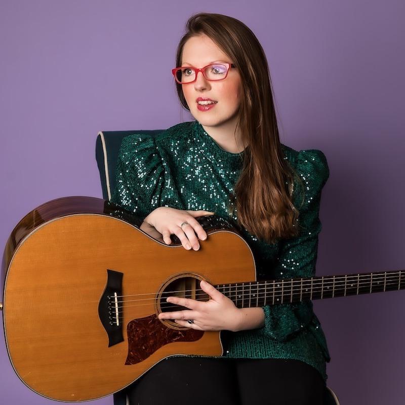 Grace Morrison press photo inside holding a guitar