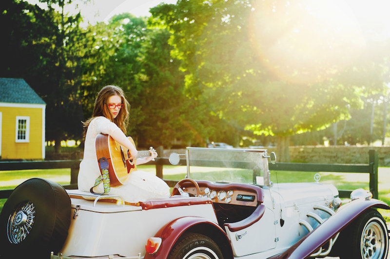 Grace Morrison press photo outside holding a guitar inside of a car