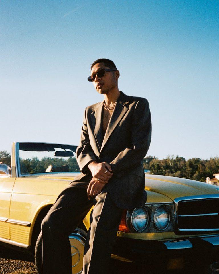 Otis Kane press photo outside sitting on the hood of a yellow convertible
