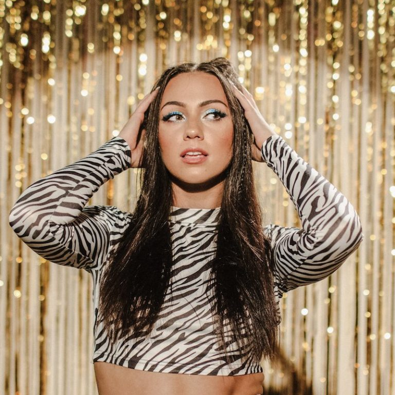Rachel Leo press photo standing in front of a glittery gold backdrop
