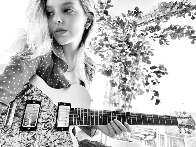 indya love press photo holding a guitar