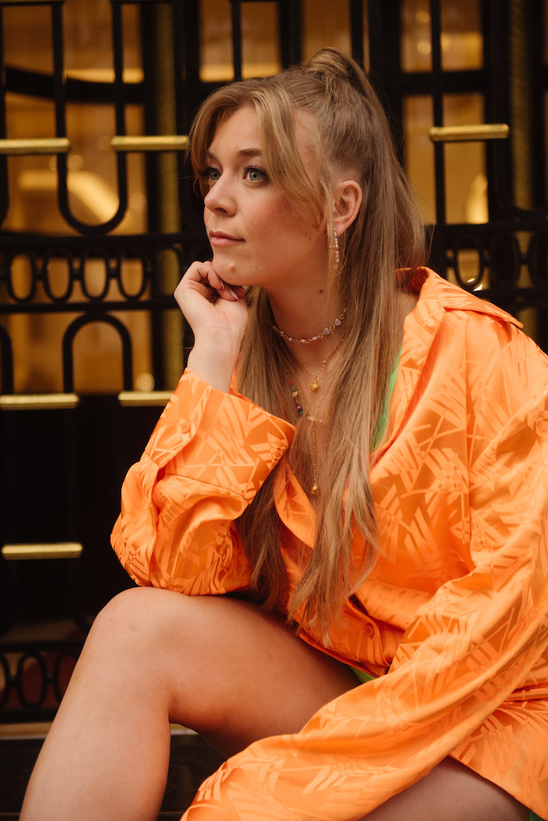 Becky Hill press photo wearing an orange and green outfit