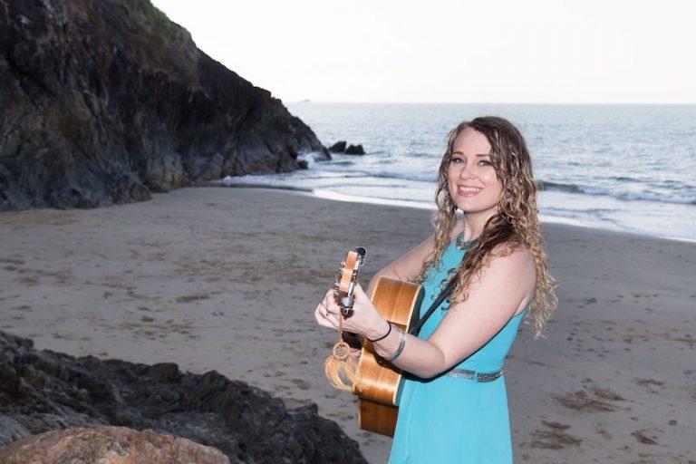 Talitha Jae press photo outside on the beach playing a guitar