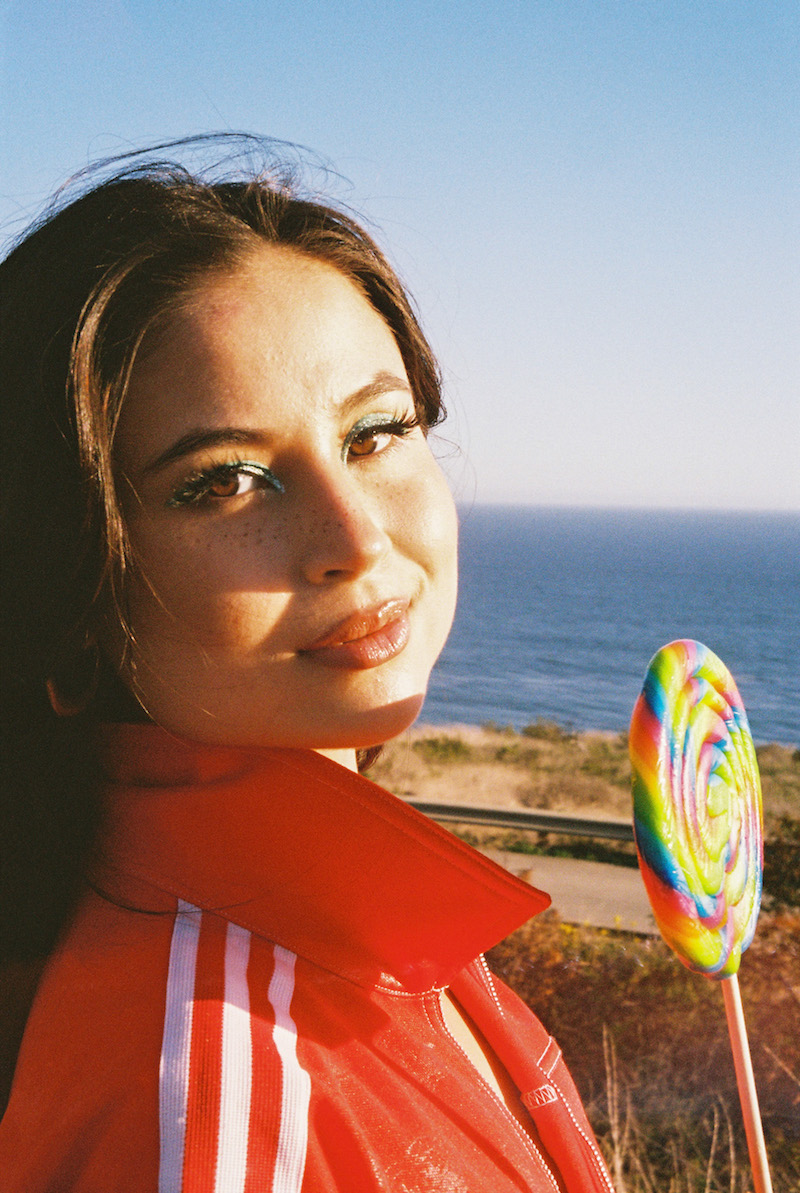 tiger lily press photo posing in front of a large body of water wearing a red jacket and holding a large colorful lollipop