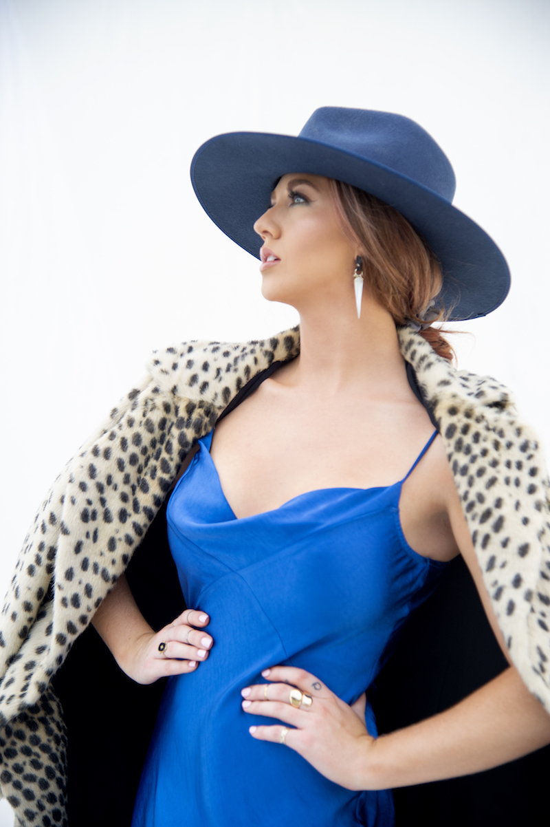 Caitlin Quisenberry press photo wearing a lush animal print coat with blue hat