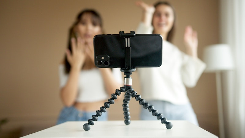 Photo of two women being recorded on a cell phone