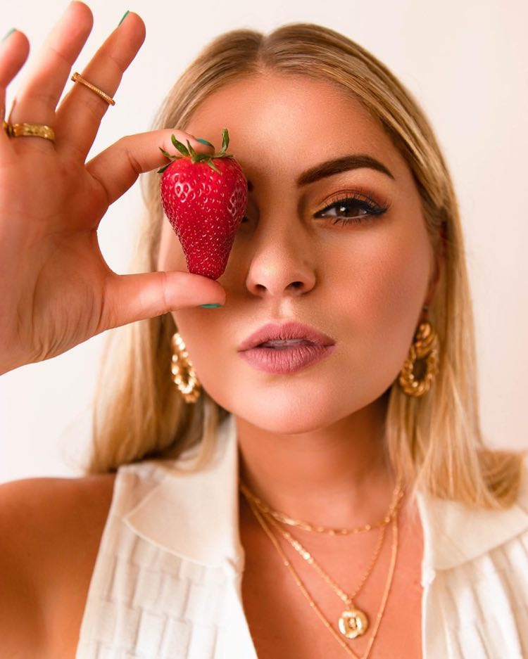 Taylor Tote press photo holding a strawberry over her right eye